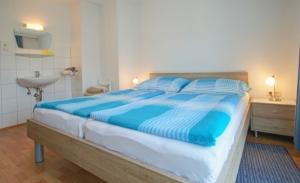 Haus Primosch Schlafzimmer in der Ferienwohnung _ Bettwäsche mit den Farben des Wörthersees in türkis-blau
